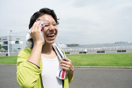 Jonge Aziatische man met behulp van een handdoek na de training in een park Stockfoto