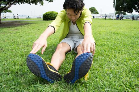 Jonge Aziatische fitness man runner stretchen voor run