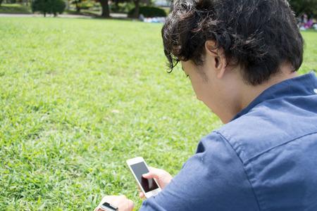 Jonge Aziatische freelance man het controleren van zijn smartphone in een park Stockfoto
