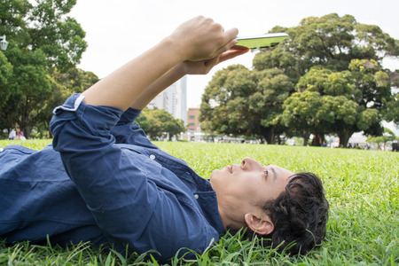 Young Asian freelance man laying down on the grass and working with tablet
