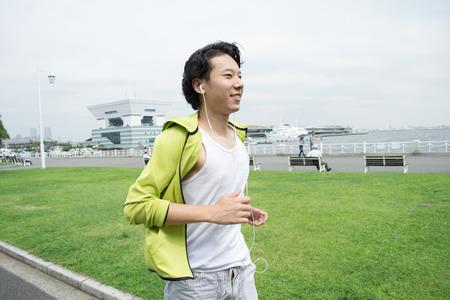 都市公園における実行して幸せな若いアジア男