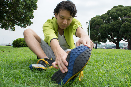 Young Asian fitness man runner stretching before run