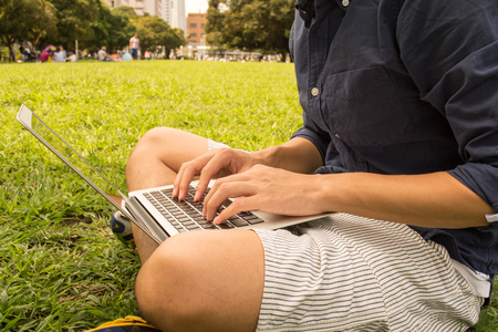 Jonge Aziatische freelance man met behulp van een pc op een park Stockfoto