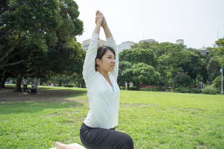 yoga outside: Young Asian fitness woman doing yoga outside on grass Stock Photo