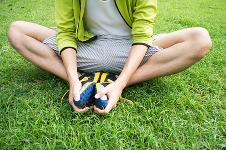 若いアジアのフィットネスの男性ランナー実行する前にストレッチ 写真素材