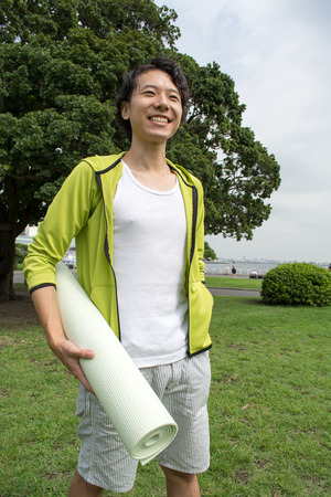 Young Asian man with a gym mat in the park Stock Photo
