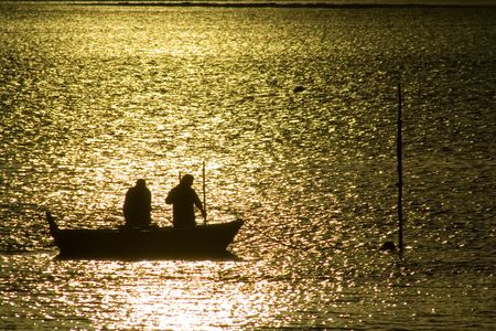 Two fisherman in water with back light photo