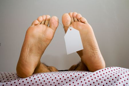 dead foots with a white tag in a bed, in a non natural position Stock Photo - 788130