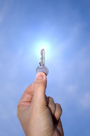 keys to heaven: A hand holding a key up in the sky Stock Photo
