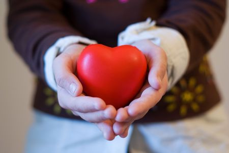 hearts and hands: The hands of a chindren holding a red heart (focus on the heart) Stock Photo