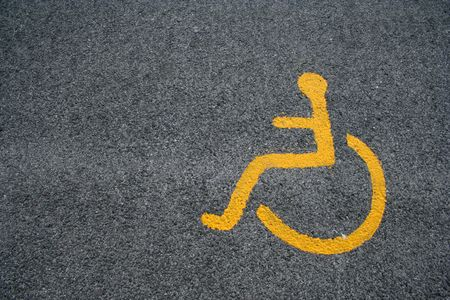 yellow sign for disabled parking on black asphalt photo