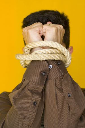 dissuade: A bussinessmen tiedup by his fists with a yellow background