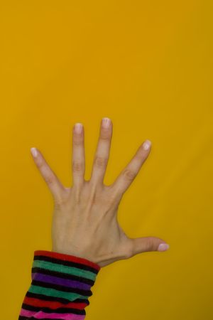 A woman showing her beautifull nails in a color background photo