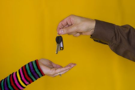 a business man passing the keys to a young woman Stock Photo - 970698
