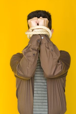 A bussinessmen tied up by his fists with a yellow background