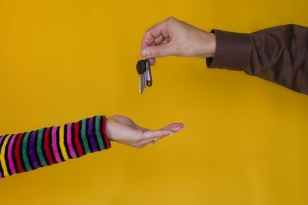 a business man passing the keys to a young woman Stock Photo - 1010163