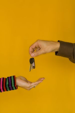 a business man passing the keys to a young woman Stock Photo - 1010164