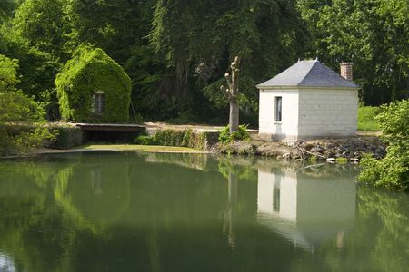 a reflection of a little house on a lake photo
