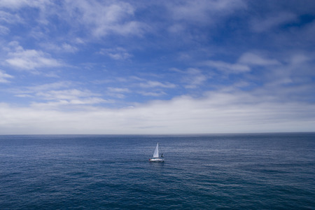 sailboat race: a lonely boat sailing in the ocean