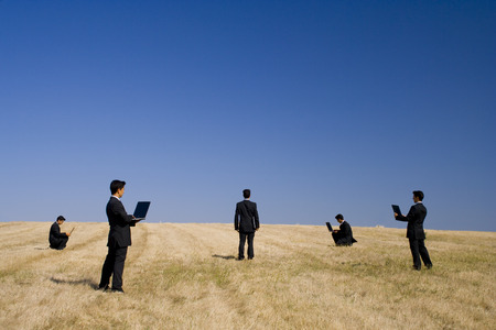 businessman working in a field making a teamwork with the nature photo