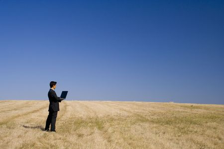 entrepeneur: a businessman working in a open field Stock Photo