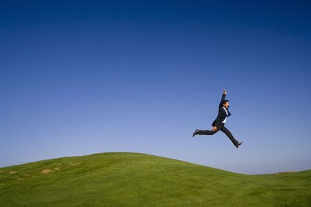 Businessman leaping on a beautiful green and blue landscape photo
