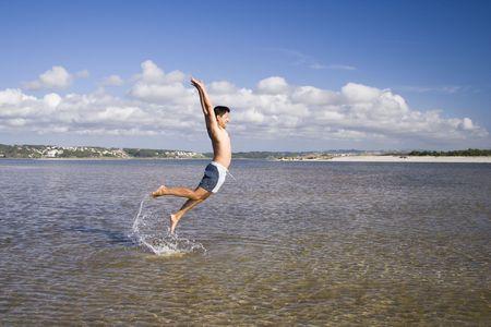 a man at the beach, jumping photo