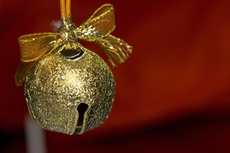 a beautiful background of a gold jingle bell on red background photo