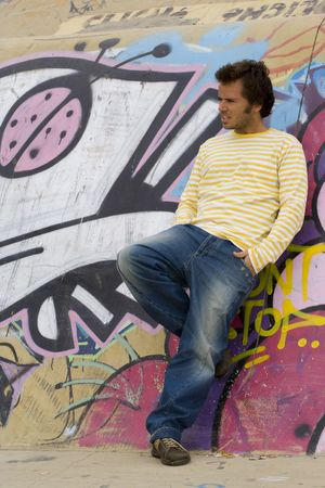 young men next to a graffiti wall, showing the urban style Stock Photo - 2114084