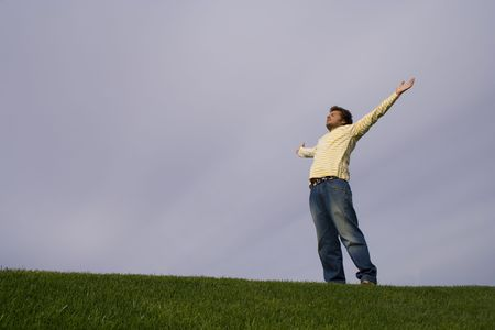 young man in the grass looking to the sky with his arms outstretched Stock Photo - 2114080