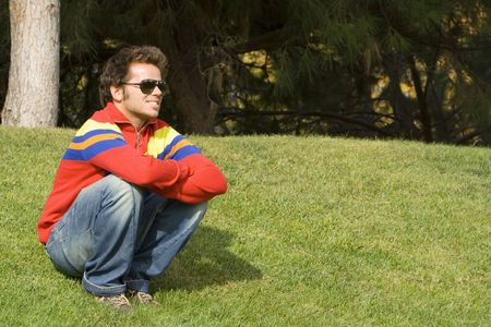 young men sit in the grass looking arround Stock Photo - 2223586