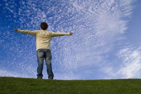 manos levantadas al cielo: el hombre joven en la hierba que miraba al cielo con sus brazos outstretched Foto de archivo