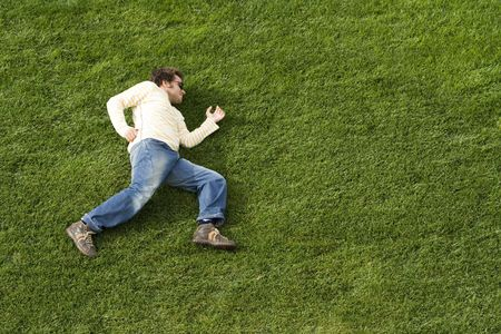 simulate: young man simulate running laying down on the grass