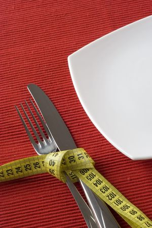 controling: Fork and knife tieup with a measure tape. Conceptual idea of controling obesity.