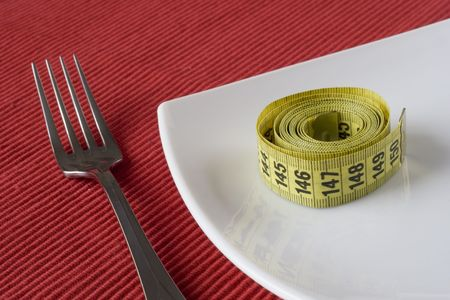 controling: Fork, plate and a measure tape. Conceptual idea of controling obesity. (selective and soft focus) Stock Photo