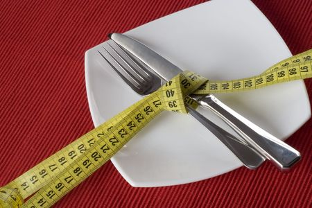 controling: Fork and knife tieup with a measure tape. Conceptual idea of controling obesity. (selective and soft focus)