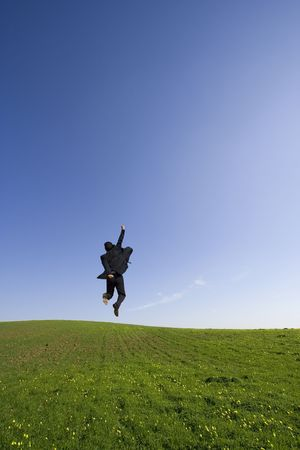 Businessman jumping on the field photo