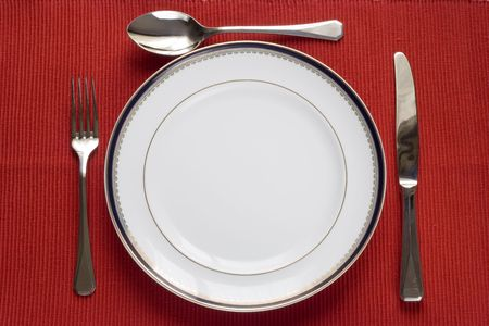 fork, knife and spoon in a porcelain plate over red (copy space in the plate) Stock Photo - 2637510