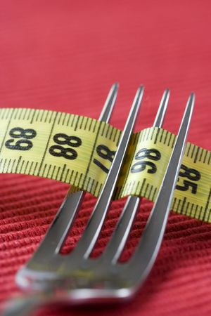 mesure: a fork and a mesure tape, conceptual loose weight (soft and selective focus)