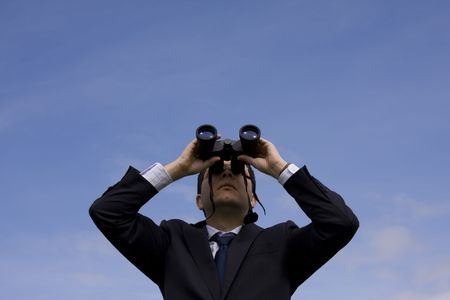 see  visionary: Businessman looking through binoculars with a blue sky as background
