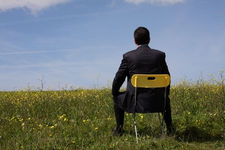 blue sky thinking: Businessman back sitting in a yellow chair Stock Photo