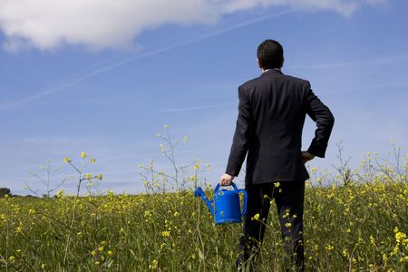 businessman at the field with a flowerpot in his hand photo