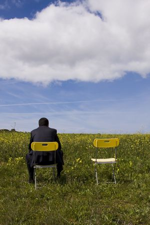 Businessman back sitting in a yellow chair waiting for his partner photo