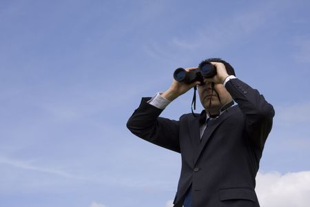 Businessman looking through binoculars with a blue sky as background Stock Photo - 2780739