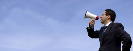Businessman speaking with a megaphone with the blue sky as background (wide format photo) photo