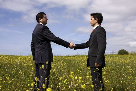 two businessmen making a deal with a handshake at the field photo