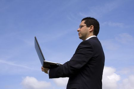 Businessman with a laptop and blue sky as background Stock Photo - 2820198