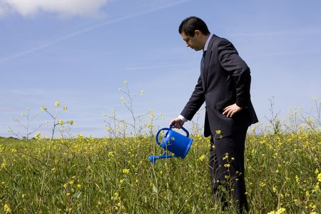 businessman at the field with a flowerpot in his hand Stock Photo - 2820223