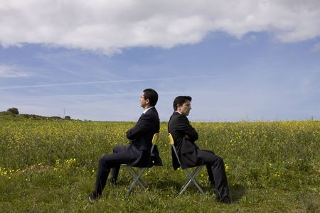 argue between two businessman in a field photo