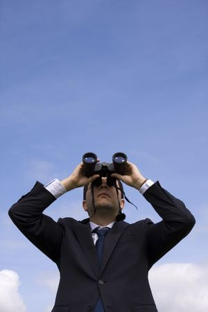 Businessman looking through binoculars with a blue sky as background  photo